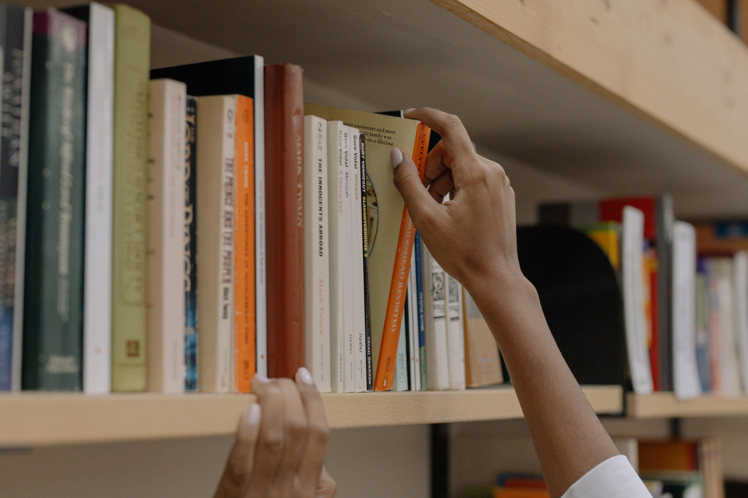 Student selecting a book off of a bookshelf