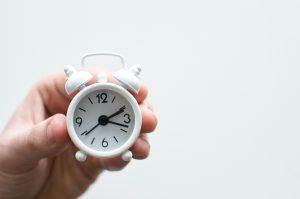 Hand holding small white alarm clock