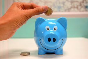 Blue piggy bank with hand adding an coin