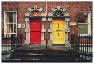 Two doors, one red and one yellow, leading into a brick building