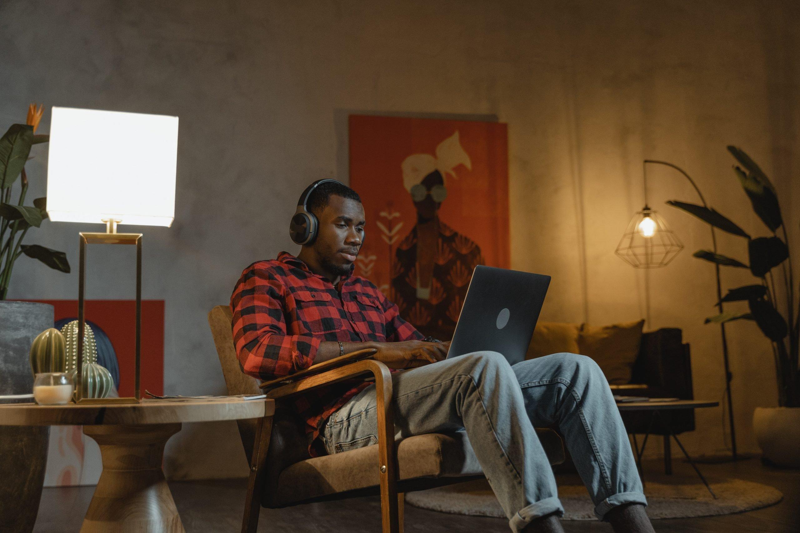 Young man studying at home with laptop and headphones
