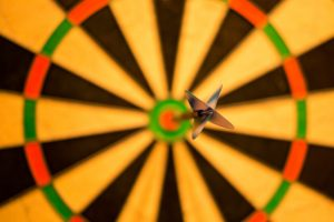 Close up of a dartboard with a dart in the bullseye